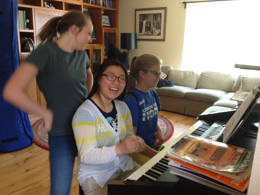 Becca singing with friends at the piano